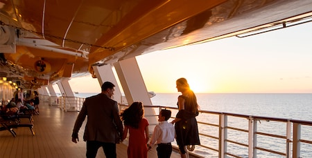 A mother, father and their son and daughter walk near the railing of a cruise ship as the sun sets over the ocean