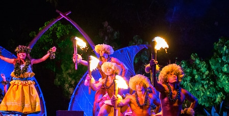 A woman hula dancer and four men with torches dressed in traditional Hawaiian garb on stage in a nighttime performance