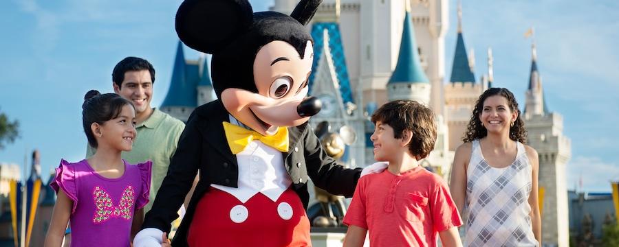 Mickey Mouse camina con 2niños y sus padres cerca del Cinderella Castle en el Parque Temático Magic Kingdom